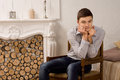 Dejected young man with a worried expression sitting in front of an ornate marble fireplace staring gloomily at the floor Stock Photography