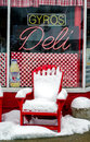 The deli shop a snow covered chair sits in front of an old fashioned in michigan Royalty Free Stock Photo