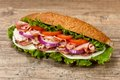 Deli sub sandwich homemade italian with salami tomato and lettuce selective focus Stock Photos