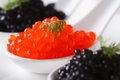 Delicacy red and black caviar fish macro horizontal in white spoons on a plate Stock Image