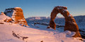 Delicate arch at sunset in winter view of covered snow arches national park Royalty Free Stock Image