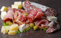 Delicatessen cold cuts arrangement of with smoked ham pepperoni salami finocchiona green olives grana padano and camembert cheese Stock Photos
