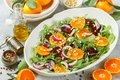 Delicatessen colorful salad of baked beets, arugula, tangerines and red onions Royalty Free Stock Photo