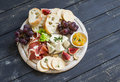 Delicious appetizer to wine - ham, cheese, grapes, crackers, figs, nuts, jam, served on a light wooden board Royalty Free Stock Photo