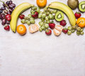 Delicious assortment of fresh fruit  laid out in a border on a white rustic background top view Superfoods and health or detox die Royalty Free Stock Photo