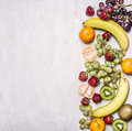 Delicious assortment of fresh fruit laid out in a border on a white rustic background top view Superfoods and health or detox die