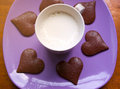 Delicious breakfast cup of milk and heart shaped pieces of chocolate on purple plate Stock Image