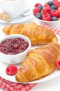 Delicious breakfast fresh croissant with raspberry jam coffee and berries on white Royalty Free Stock Image