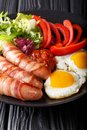 Delicious breakfast of fried sausages wrapped in bacon, eggs and Royalty Free Stock Photo