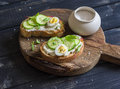 Delicious breakfast or snack - open sandwich with goat's cheese and cucumber and boiled quail eggs Royalty Free Stock Photo