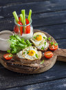 Delicious breakfast or snack -  sandwich with cheese and a fried quail egg, greek yogurt, celery and sweet peppers on rustic woode Royalty Free Stock Photo