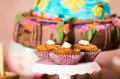 Delicious brown colored muffins with caramel sauce and cream topping, colorful cake in background, pastry concept Royalty Free Stock Photo