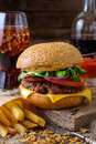 Delicious burger with chips and soda on wooden table. Royalty Free Stock Photo