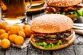 Delicious burger with fried potato balls and beer Royalty Free Stock Photo