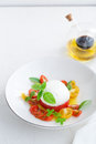 Delicious caprese salad with ripe cherry tomatoes and mozzarella cheese with fresh basil leaves and olive oil. Italian Royalty Free Stock Photo