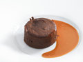 Delicious chocolate fondant with caramel sauce served on a white round plate isolated on white Stock Photos