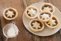 Delicious christmas mince pies with stars preparing a plate of decorated pastry and sprinkling them icing sugar from a sieve Stock Photography