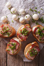 Delicious crostini with bacon and mozzarella closeup. vertical t Royalty Free Stock Photo