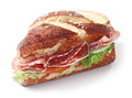 Delicious crusty brown lye bread roll sandwich a traditional german and bavarian glazed with with spicy salami sausage Stock Images