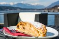 Delicious desert at a lakeside bar traditional apple strudel surrounded by mountains Royalty Free Stock Image