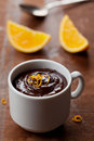 Delicious dessert from dark chocolate mousse with orange slice decorated citrus peel on rustic table Stock Image