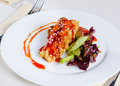 Delicious dish of saucy fried chicken with veggies close up main crispy in beautiful plating style on white round plate Stock Image