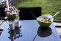 Delicious fresh healthy salad green bowl with salad spoon food standing on a the table with flowers Royalty Free Stock Photo