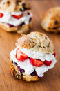 Delicious freshly baked scones filled with thick clotted cream jam and fresh strawberries Royalty Free Stock Photos