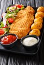 Delicious fried fillet of white fish in breading with a side dish of new potatoes and fresh vegetable salad close-up. vertical Royalty Free Stock Photo
