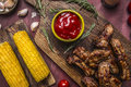 Delicious fried lamb ribs grilled with spicy sauce, herbs and corn on wooden rustic background top view close up Royalty Free Stock Photo