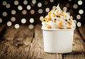 Delicious frozen yogurt party dessert twirled in a tub and decorated with sprinkles against a sparkling bokeh of festive lights Royalty Free Stock Photography