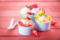 Delicious fruit and berries with frozen yoghurt fresh tropical assorted served or ice cream in three individual servings on a pink Stock Photos