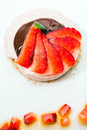 Delicious fruit tarts sweet tart with chocolate and strawberry cream decorated with strawberry pieces on white plate Royalty Free Stock Image