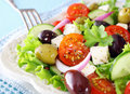 Delicious greek salad with feta cheese olives tomato cucumber and crispy lettuce garnished chopped parsley Stock Photography