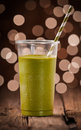 Delicious green vegetable smoothie standing on a rustic wooden counter against a brown toned bokeh of party lights Royalty Free Stock Images