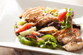Delicious grilled chicken salad freshly prepared chef style with tomato cucumber green pepper and romaine lettuce Stock Photos