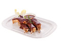 Delicious grilled pork ribs served with a rich brown gravy or bbq sauce garnished with fresh herbs close up side view Royalty Free Stock Images