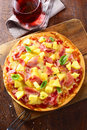 Delicious ham and pineapple pizza overhead view of a freshly baked on a thin crispy crust standing on an old wooden board on a Stock Images