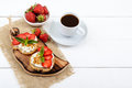 Delicious healthy dietary breakfast: rye bread with cottage cheese and strawberries and a cup of coffee espresso Royalty Free Stock Photo