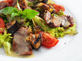 Delicious healthy warm salad with beef and vegetables on a round plate Stock Photography