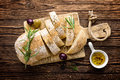 Delicious homemade italian ciabatta bread with olive oil and olives on wooden rustic background, above view, space for text Royalty Free Stock Photo