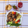 Delicious juicy grilled steak, vegetables and mushrooms on the plate, surrounded by tomatoes, fresh herbs and red barbecue sauce. Royalty Free Stock Photo