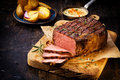 Delicious lean rare roast beef seasoned with fresh herbs and rosemary and carved ready to serve with golden potatoes Stock Photo