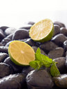 Delicious mint and lime fruit, black stones. Royalty Free Stock Photos