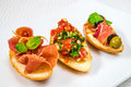 Delicious, mouth-watering different canapes with meat, vegetables, herbs and olives, on a white plate. Horizontal frame