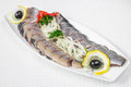 Delicious, mouth-watering slices of sliced herring with onion rings, lemon and herbs, on a white plate. Horizontal frame