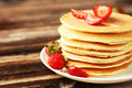 Delicious pancakes with strawberry on brown wooden background a Stock Images