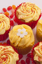 Delicious pineapple and rhubarb cupcakes cupcake with a icing sugar flower on the top some jelly beans around Royalty Free Stock Images