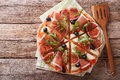 Delicious pizza with figs, ham, arugula and cheese macro. horizo Royalty Free Stock Photo