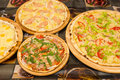 Delicious pizzas with variety of toppings and cheese on wooden t Royalty Free Stock Photo